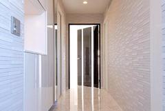 大理石調の床とセラミックタイルで仕上げたモダンな玄関。