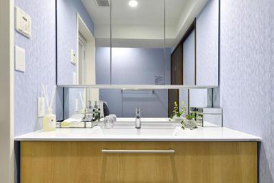ブルーの壁と木目のコントラストが美しいさわやかな洗面室。
